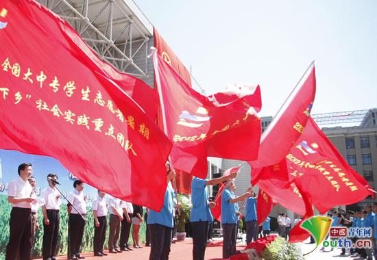 学生代表们在台上舞动团队旗帜.-绿色新闻网